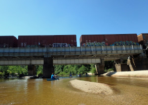 Paddlers passing beneath the railroad trestle.